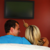 young couple pointing at tv